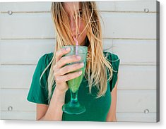 Young Blond Woman In A Green Top, Drinking Juice Acrylic Print by Matilda Delves
