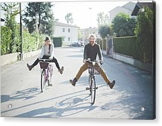 Young Couple Cycling With Legs Out Acrylic Print by Eugenio Marongiu