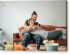 Young Couple With Smart Phone Relaxing On Sofa Acrylic Print by Luis Alvarez