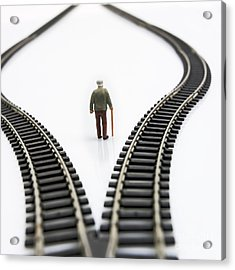 Figurine Between Two Tracks Leading Into Different Directions Symbolic Image For Making Decisions. Acrylic Print by Bernard Jaubert