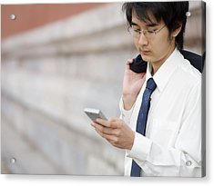 A Young Businessman Checks His Text Acrylic Print by Justin Guariglia
