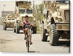An Iraqi Boy Rides His Bike Past A U.s Acrylic Print by Stocktrek Images