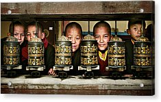 Buddhist Monks In Red Robes Look Out Of The Prayer Wheels With M Acrylic Print by Max Drukpa