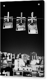 Three Twenty Euro Banknotes Hanging On A Washing Line With Blue Sky Over City Skyline Acrylic Print by Joe Fox