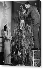 Woman Assisting Man Placing Star On Top Of Christmas Tree, (b&w) Acrylic Print by George Marks