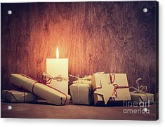 Chistmas Presents, Gifts With A Candle Glowing On Wooden Wall Background. Acrylic Print