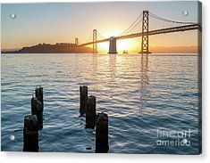 Six Pillars Sticking Out The Water With Bay Bridge In The Backgr Acrylic Print
