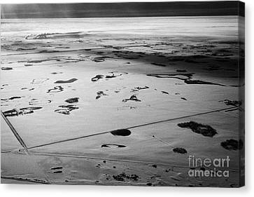 aerial view of snow covered prairies and remote isolated farmland in Saskatchewan Canada Canvas Print