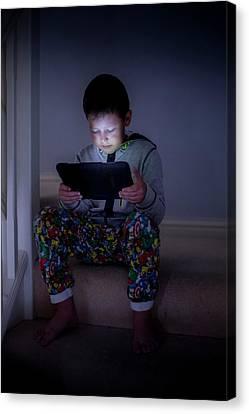 Boy Using A Digital Tablet In The Dark Canvas Print by Samuel Ashfield