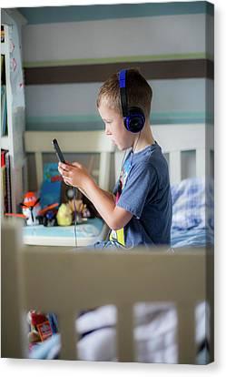Boy Wearing Headphones Using Device Canvas Print