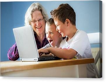 Boys Using Laptop With Grandmother Canvas Print by Samuel Ashfield