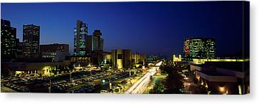 Buildings In A City Lit Up At Night Canvas Print by Panoramic Images