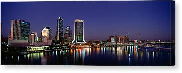 Buildings Lit Up At Night Canvas Print by Panoramic Images