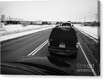 cars waiting on train crossing trans-canada highway in winter outside Yorkton Saskatchewan Canada Canvas Print