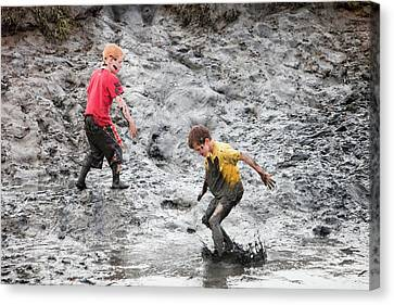 Children Playing In A Muddy Creek Canvas Print by Ashley Cooper