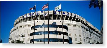 Flags In Front Of A Stadium, Yankee Canvas Print by Panoramic Images