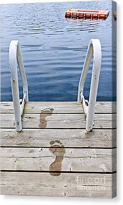 Footprints On Dock At Summer Lake Canvas Print by Elena Elisseeva