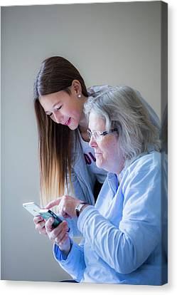 Girl Showing Grandmother Smartphone Canvas Print by Samuel Ashfield