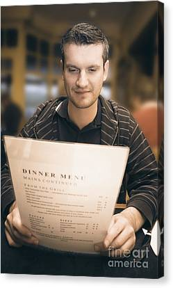 Man In Mid 20s Reading Restaurant Dinner Menu Canvas Print by Jorgo Photography - Wall Art Gallery