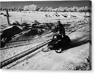 man on snowmobile crossing frozen fields in rural Forget Saskatchewan Canada Canvas Print