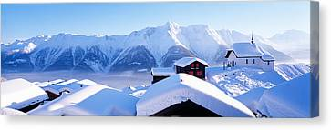 Swiss Canvas Print - Snow Covered Chapel And Chalets Swiss by Panoramic Images