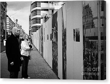 tourists read the history of the berlin wall at checkpoint charlie Berlin Germany Canvas Print