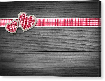 Two Hearts Laying On Wood  Canvas Print by Aged Pixel