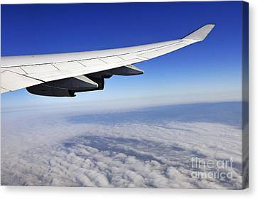 Wing Of Flying Airplane Above Clouds Canvas Print by Sami Sarkis