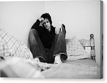 Young Dark Haired Teenage Man Sitting At The Far End Of His Bed In An Untidy Bedsit Bedroom Curled U Canvas Print by Joe Fox