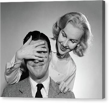 Hands Behind Head Canvas Print - 1950s Woman Standing Behind Man by Vintage Images