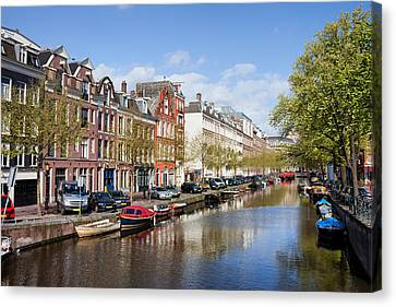 Boats On Amsterdam Canal Canvas Print by Artur Bogacki