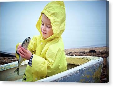 Boy Wearing Raincoat Holding A Mackerel Canvas Print