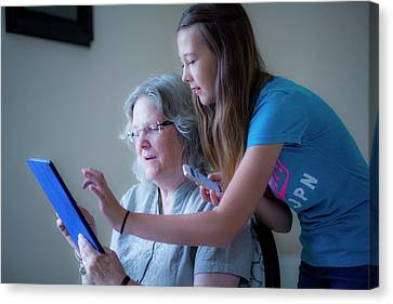 Girl And Grandmother Using Tablet Canvas Print by Samuel Ashfield