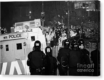 Psni Riot Officers Face Rioters Mob On Crumlin Road At Ardoyne Shops Belfast 12th July Canvas Print by Joe Fox