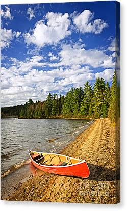 Red Canoe On Lake Shore Canvas Print by Elena Elisseeva