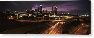 Skyscrapers Lit Up At Night In A City Canvas Print by Panoramic Images