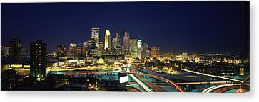 Buildings Lit Up At Night In A City Canvas Print