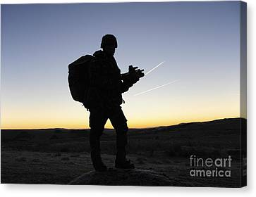 A British Soldier On Patrol As The Sun Canvas Print by Andrew Chittock
