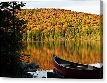 A Canoe On The Shoreline Of Pond Canvas Print by Jerry and Marcy Monkman