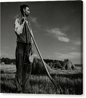 Hay Bales Canvas Print - A Farmer Holding A Pitchfork by Roger Schall