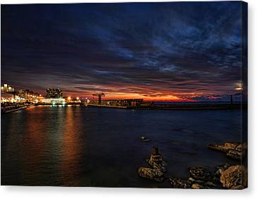 Canvas Print featuring the photograph a flaming sunset at Tel Aviv port by Ron Shoshani