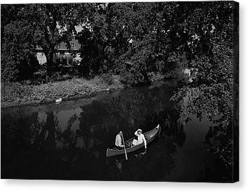 A Man And Woman In A Canoe On A Lake Canvas Print by Roger Sturtevant