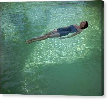 Fashion Model Canvas Print - A Model Floating In A Swimming Pool by John Rawlings