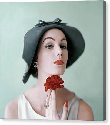 A Model Wearing A Hat And Holding A Flower Canvas Print