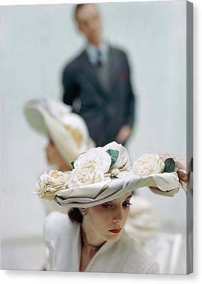 A Model Wearing A Hat Decorated With Flowers Canvas Print by John Rawlings