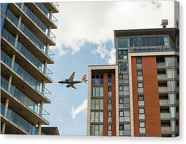 A Plane Flying Past Apartment Blocks Canvas Print by Ashley Cooper