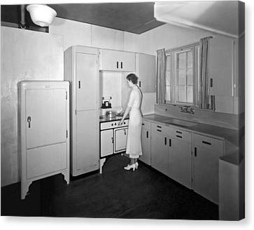 A Woman In Her Kitchen Canvas Print by Underwood Archives
