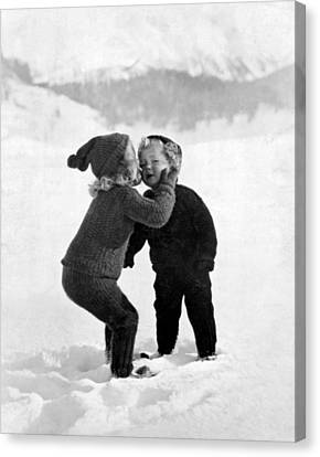 A Young Girl Gives Her Little Brother A Kiss On The Cheek In The Snow Canvas Print by Unknown Photographer