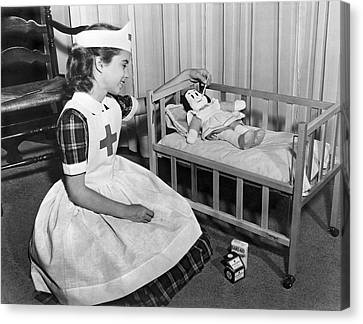 A Young Girl Plays Nurse To Her Little Lulu Doll. Canvas Print by Underwood Archives