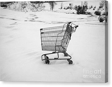 abandoned shopping cart in snow covered supermarket parking lot Saskatoon Saskatchewan Canada Canvas Print